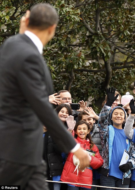 Back on the campaign trail: Mr Obama waves to children waiting on the White House lawn before heading back on the campaign trail in Wisconsin, Nevada, and Colorado