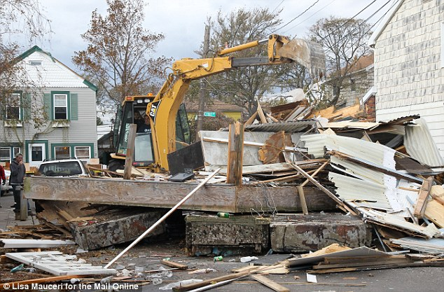 Condemned: The digger reduces the venue to a pile of debris under police direction