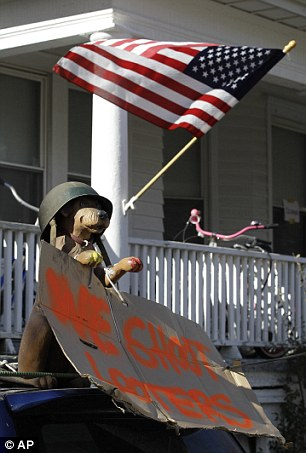 Shooting looters: A toy dog wearing a military helmet sits atop a car holding a sing warning off looters in a resident's driveway in the Rockaways
