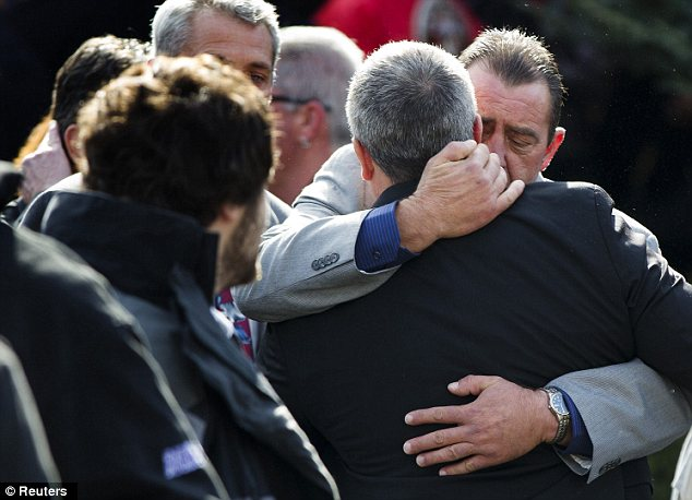 Tragedy: Mourners embrace following the funeral of them men, who drowned together in the storm surge caused by Superstorm Sandy
