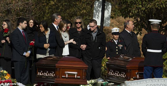 Heartbreak: Christine Filipowicz, pictured center, is consoled by her children Cali, 16, left, and Joseph, right, as they stand before the coffins of her husband and son