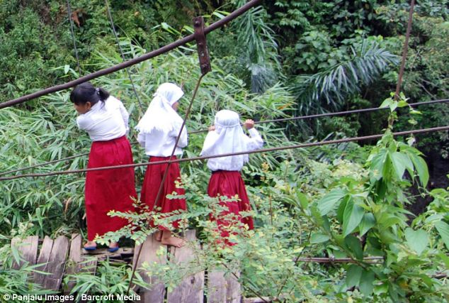 Three schoolgirls wait to cross the river on the high wire after heavy rains destroyed the bridge more than two years ago