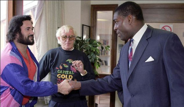 Former boxer Frank Bruno, right, pictured at Broadmoor in 1991 shaking hands with Yorkshire Ripper Peter Sutcliffe as Savile stands in the background. Frank says he was tricked into shaking hands with the murderer