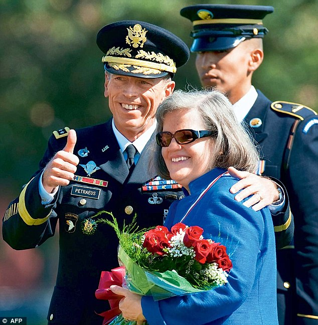 Former US Army General David Petraeus gives a thumbs-up after presenting his wife Holly with a bouquet of roses in 2011