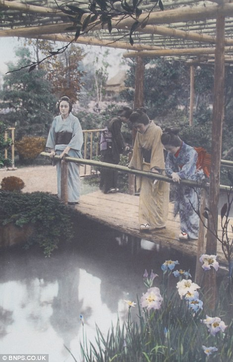 Geisha's look at their reflections in a landscaped garden pond
