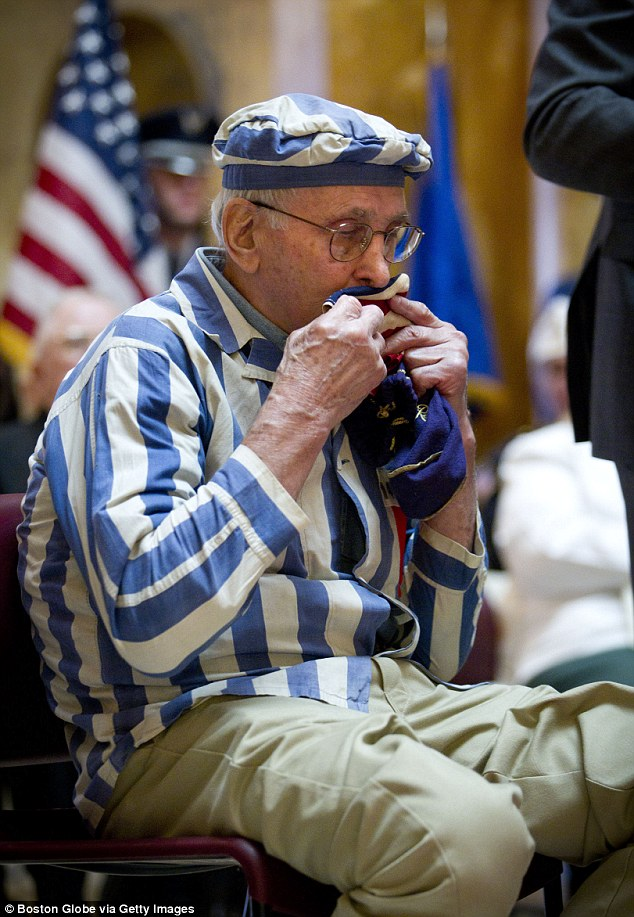 Poignant memento: Stephan Ross, dressed in a uniform like one he was forced to wear in the Nazi camps, kisses the handkerchief-flag that was given to him by an American soldier in 1945