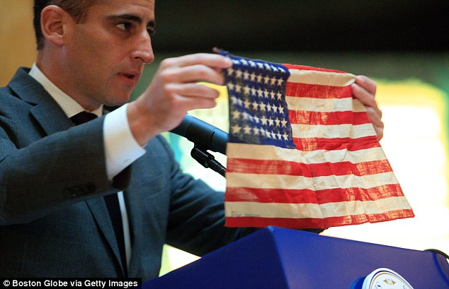 Symbolic gesture: Mr Ross's son and Boston City Councillor Michael Ross holds up the flag his father received from an American soldier at Dachau concentration camp in Germany almost seven decades ago