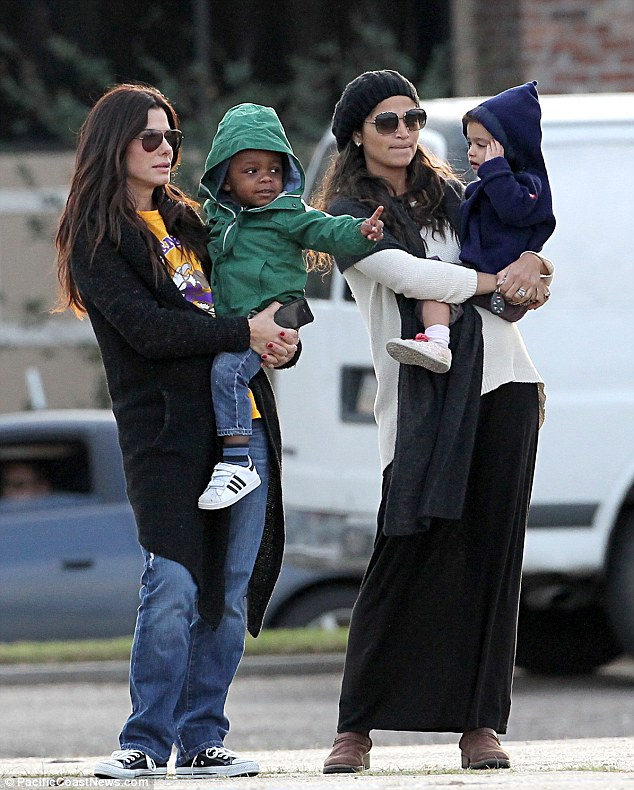 Compairing notes? Sandra Bullock and Camila Alves McConaughey take their children to support a New Orleans high school on Tuesday