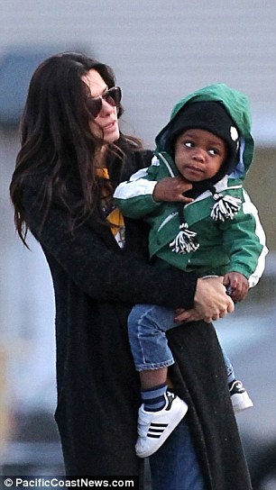 Doting mum: Sandra keeps two-year-old son Louis close as they watch a marching band perform