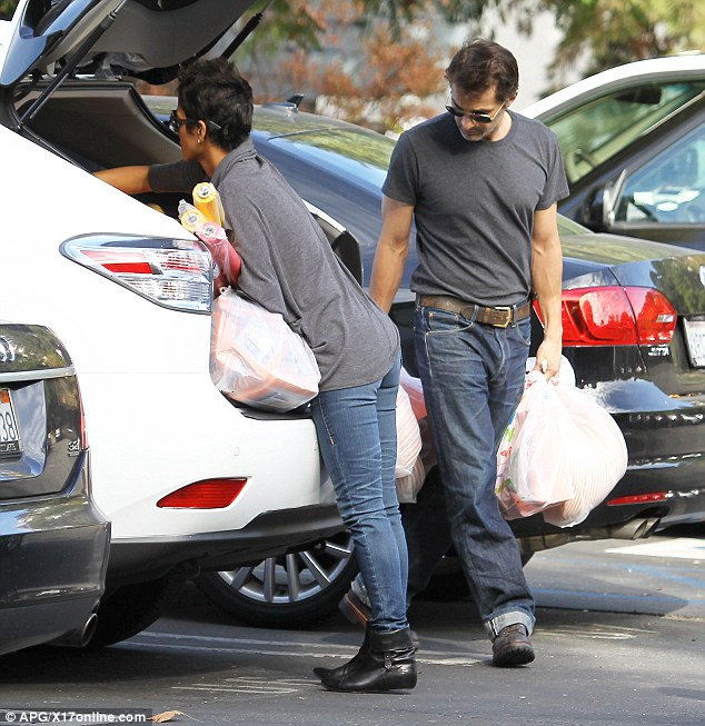 Helping hand: Halle's boyfriend Olivier Martinez was there to carry some of the bags of napkins, cups and paper