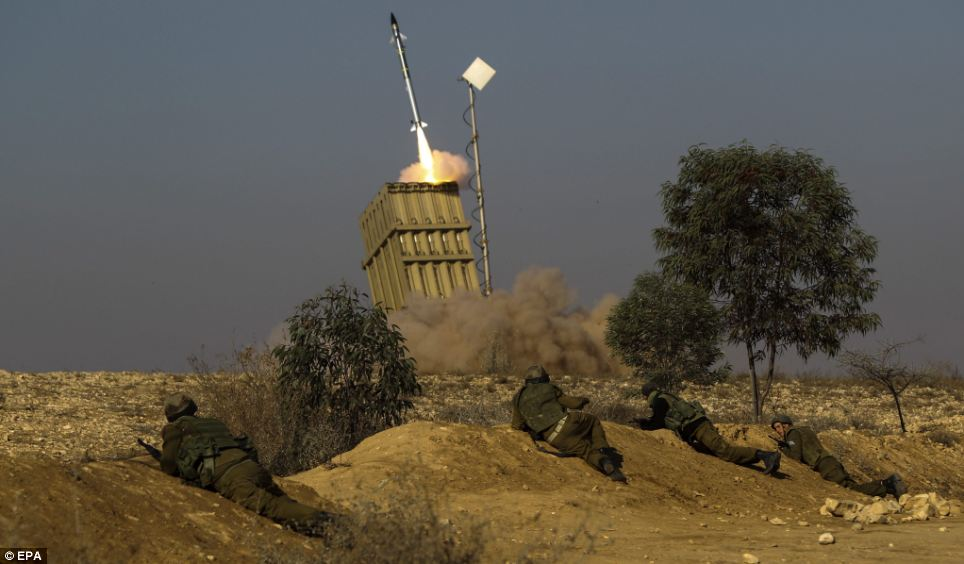 Operation: Israeli soldiers take cover as the 'Iron Dome' fires a missile against a Grad missile fired from the Gaza Strip, as it defends an Israel