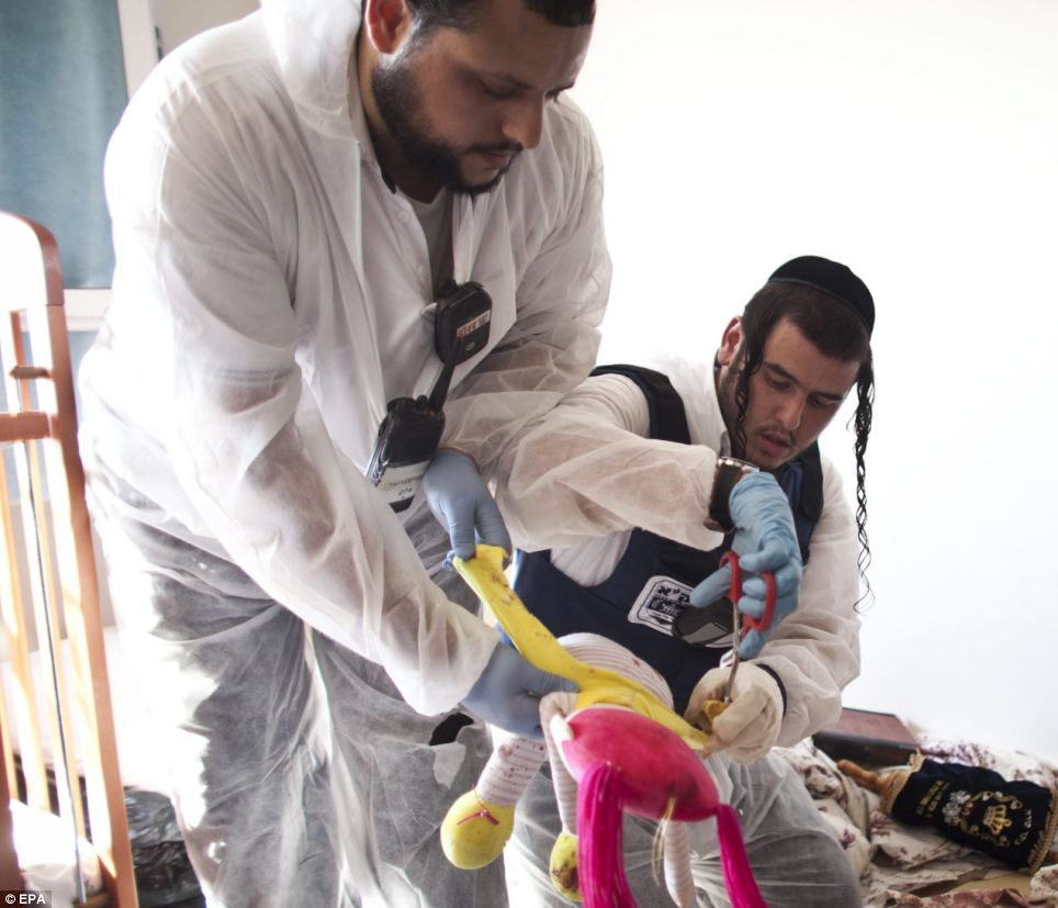 Clean-up: Zaka volunteers clean blood stains from a toy in a children's room in an apartment building that was hit by a rocket fired from the Gaza Stri