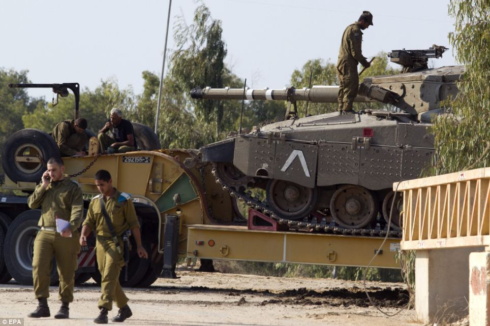 Preparing: An Israeli Merkava tank is prepared to back up from its truck carrier as equipment is brought to the Gaza Strip border in southern Israel
