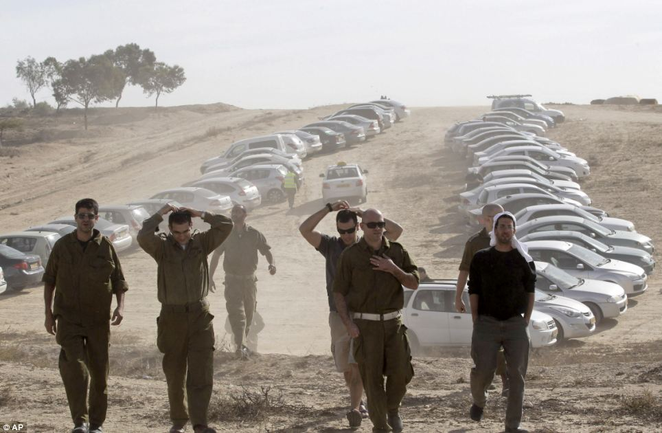 Gathering: Israeli military reservists arrive at a gathering point in Mishmar Hanegev, southern Israel earlier today