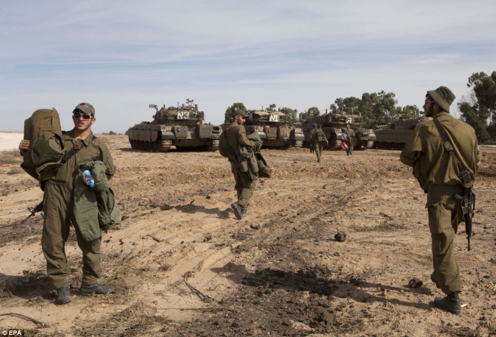 Force: Israeli soldiers return with their gears to their tanks that are parked in a staging area, along the Gaza Strip border. There are fears a land invasion could be on the way