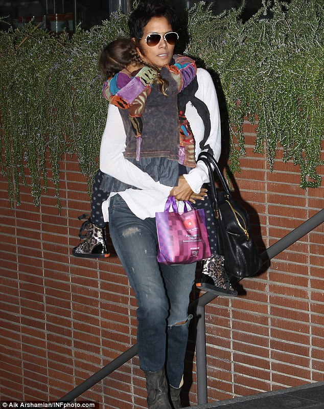 Goodies: Halle carried a pink bag of presents as she carried Nahla to the movies, her daughter was sporting some very funky shoes
