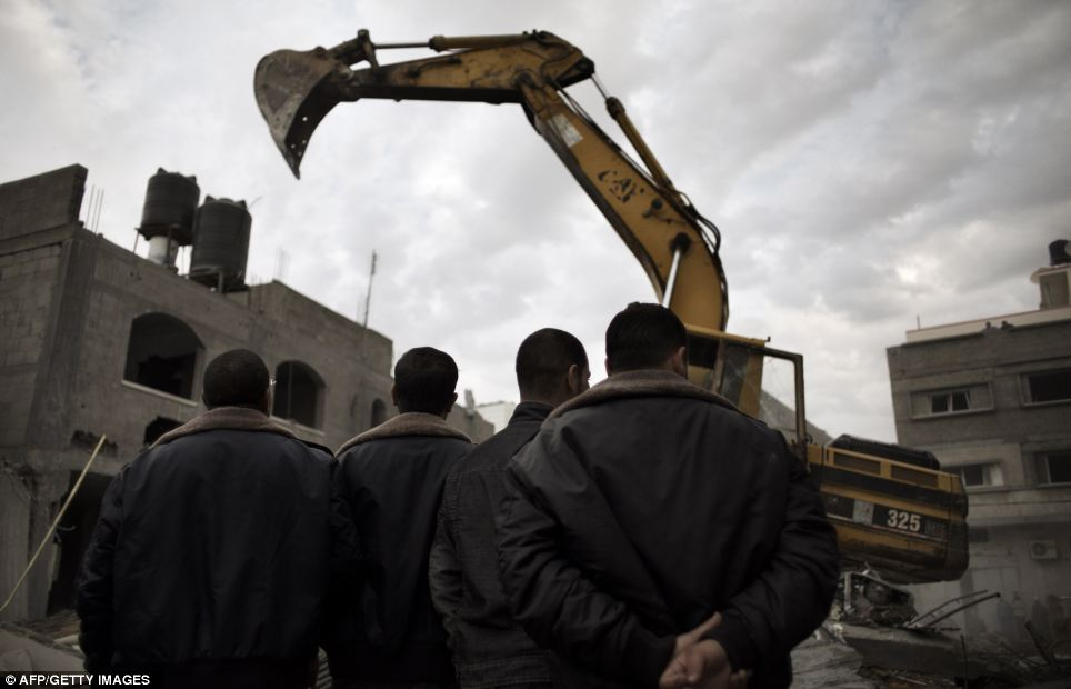 Chaos: Palestinians observe rubble being removed from the site of an Israeli air raid in Gaza today