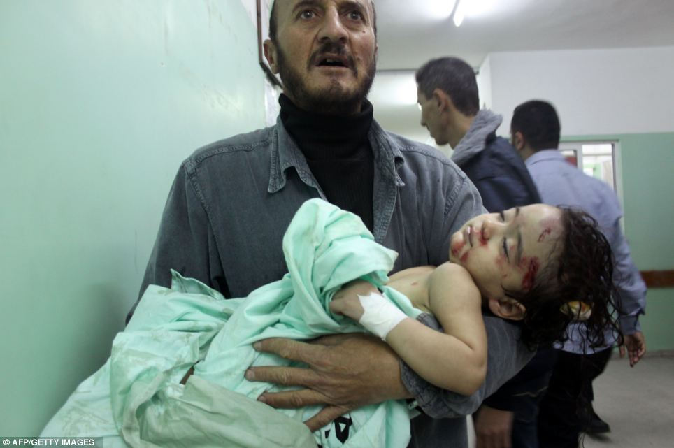 A Palestinian man carries the wounded child into a hospital ward for treatment following an Israeli air raid in Beit Lahia, northern Gaza Strip, on Saturday