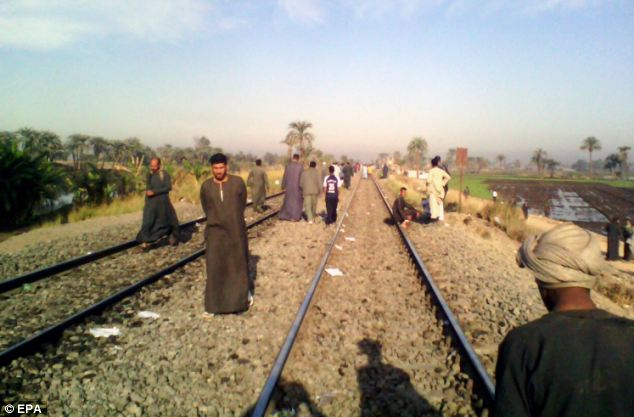 People are seen walking on train tracks after the crash, which left at least 44 children dead