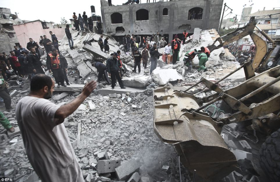 Palestinians search for victims beneath the rubble of the destroyed house of a Hamas official, following an Israeli air strike in Jabaliya refugee camp in the northern Gaza Strip today