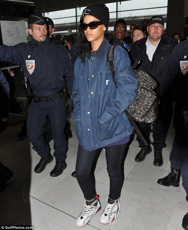 Me and my posse: Rihanna dressed down in a denim jacket and jeans as she walked through the airport