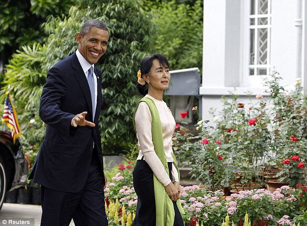 Happy to be hosted: Now a member of parliament, Suu Kyi lives in a gated residence with razor wire along the top of the compound walls which is where she hosted Obama and Clinton