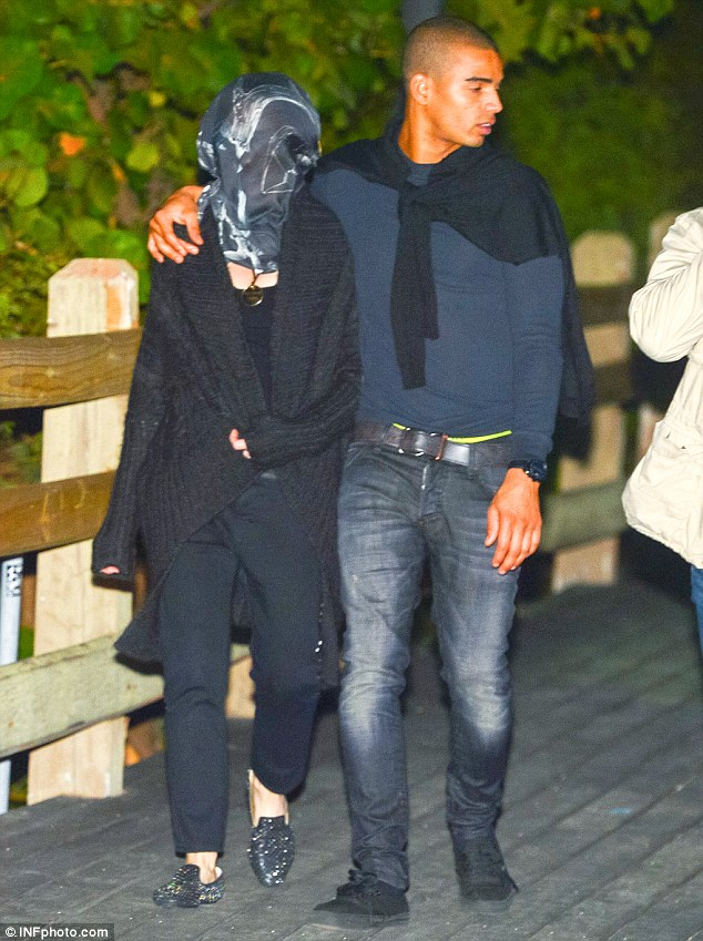 We can still see you! Madonna covers her face like Elephant Man Joseph Merrick but boyfriend Brahim Zaibat gives her identity away by walking with his arm around the star