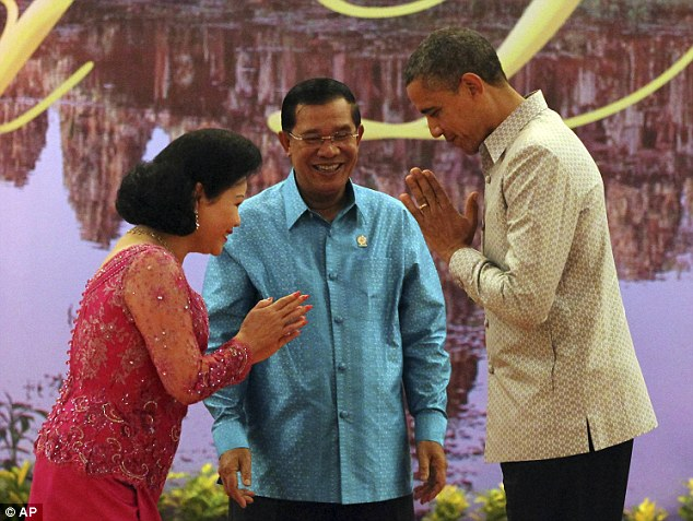 Welcome: President Obama, wearing a traditional silk shirt, returns a greeting to Bun Rany, wife of Cambodian Prime Minister Hun Sen, who stands centre, before a dinner in Phnom Penh, Cambodia