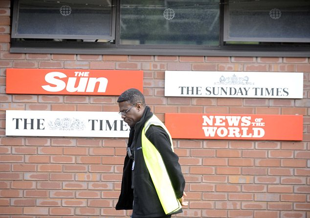 Under a cloud: A security guard walks past News International's headquarters in Wapping, London. Of the 52 arrests made under Operation Elveden, 21 are understood to be journalists at the Sun newspaper