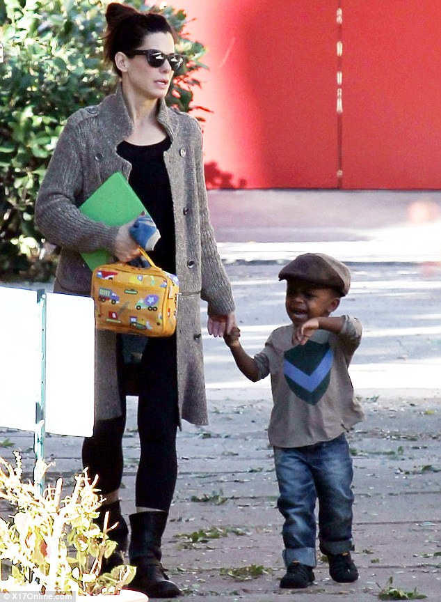 No need to cry baby: Sandra Bullock is on hand to cheer son Louis up after he bursts into tears during a trip out