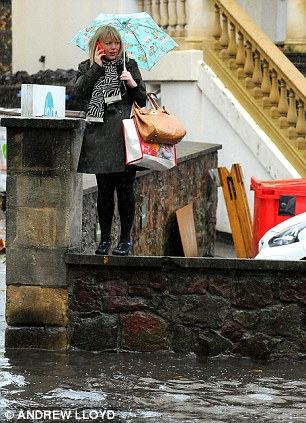 Yep, I'm going to need a boat: A woman makes a phone call from a high vantage point on Whiteladies Road in Bristol, as flood water laps beneath her