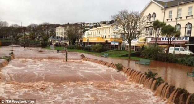 Torrent: Park benches sit submerged in muddy flood water in Dawlish, Devon on Wednesday