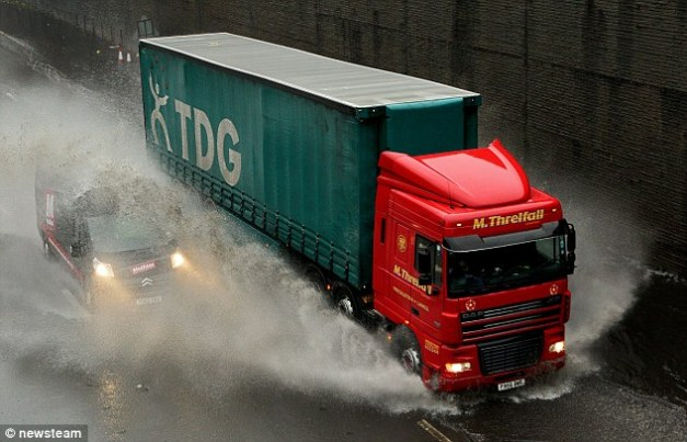 Dangerous: A van is almost invisible in the spray coming from a lorry's tyres on the M5 in Birmingham on Wednesday