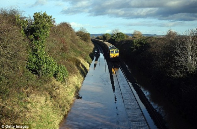 Bit more than leaves on the line: A train waits to pass along flooded track close to the village of North Curry near Taunton, Somerset, on Wednesday