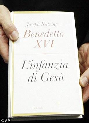 Monsignor Georg Gaenswin, Pope Benedict XVI's personal secretary, holds a copy of Pontiff's new book