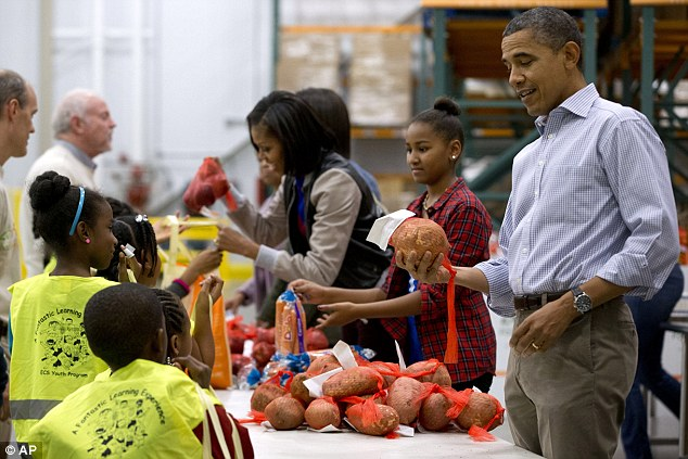 Volunteer-in-chief: President Barack Obama, right, next to daughter Sasha and first lady Michelle Obama, holds a huge sweet potato at the Capital Area Food Bank