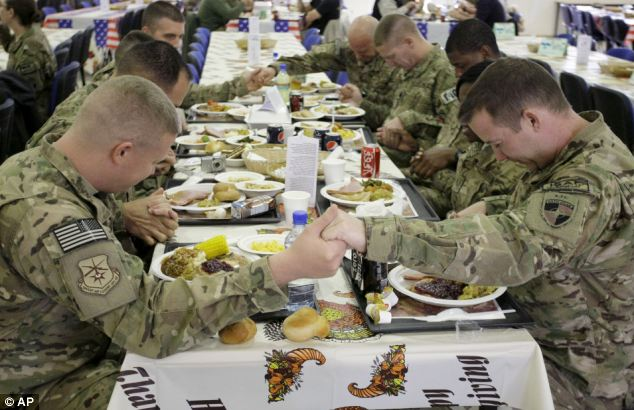 U.S. soldiers pray before eating a Thanksgiving meal at a dining hall in Kabul, Afghanistan