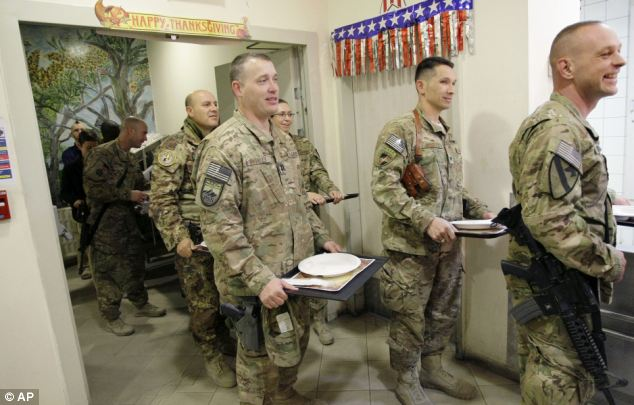 U.S. soldiers and NATO service members stand in line for mac-and-cheese and other traditional Thanksgiving Day fixings