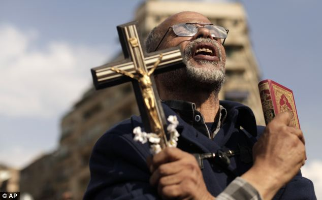 An Egyptian protester chants slogans and holds a cross and a Quran in Tahrir Square
