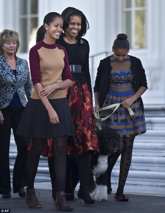 Christmas cheer: The Obama ladies walk outside the house with Bo to inspect their Christmas Tree