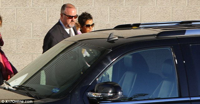 Protection: Halle carries her daughter while her bodyguard waits with her outside her vehicle