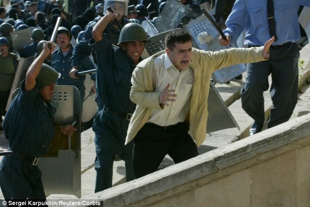Violent clash: Azeri riot police beat a man during a protest in 2003 after the rigged election which saw Ilham Aliyev was declared the winner