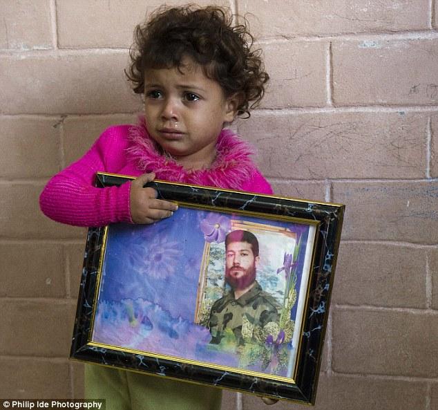 Llorosa y asustada: Tres - años de edad, Baraa (cuyo nombre significa inocencia), los embragues de una foto de su padre, que fue ejecutado públicamente y arrastrado por las calles de Gaza por una turba de linchamiento motocicleta