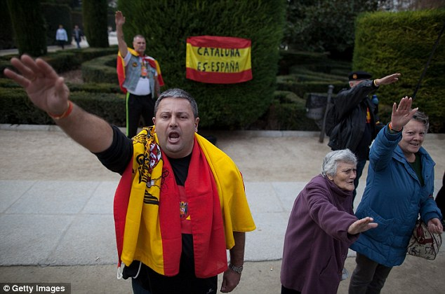 Joining in: A supporter of General Franco is joined by pensioners, one of whom can barely raise her arm to make the fascist salute before a flag bearing the slogan 'Catalonia is Spanish'