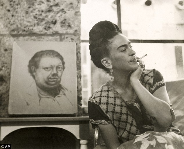 A photograph of the artist, circa 1945, with a painting of her husband Diego Rivera