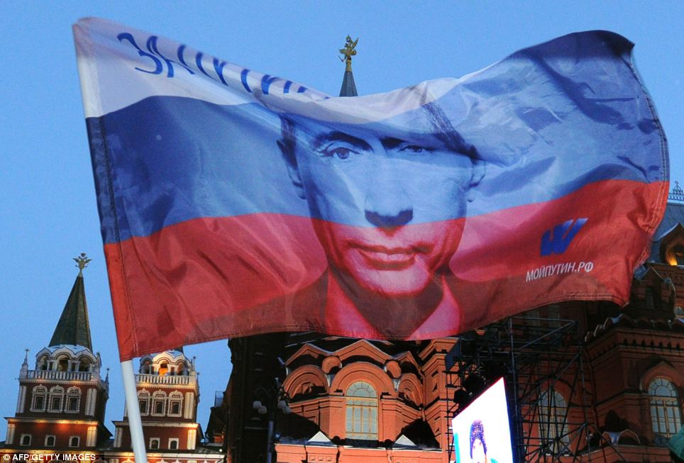 A Russian flag with Prime Minister Vladimir Putin image on it flies above his supporters as they celebrate Putin's victory at the central Manezhnaya Square just outside the Kremlin in Moscow