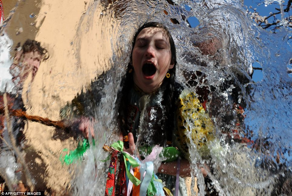Young Slovaks dressed in traditional costumes throw a bucket of water at a girl as part of Easter celebrations in the village of Trencianska Tepla, north of Bratislava, in April