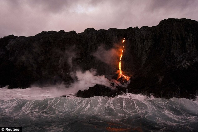 Battle of the elements: Lava from the volcano, which has been erupting continuously from its Pu'u O'o vent since 1983, reached the ocean at the weekend