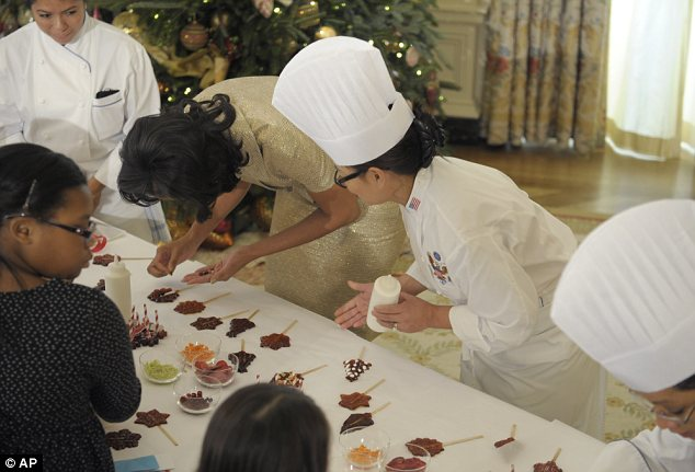 All in the detail... Mrs Obama decorates a lollipop with the help of the White House chefs