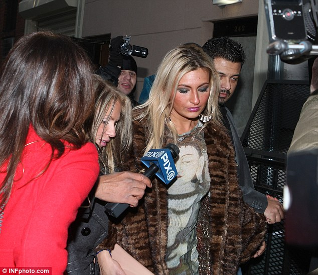 Fur coat: A blonde woman, believed to be one of Lindsay Lohan's victims, leaves a New York police station this morning